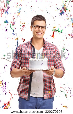 Vertical shot of a young man carrying a birthday cake with confetti all around him isolated on white background