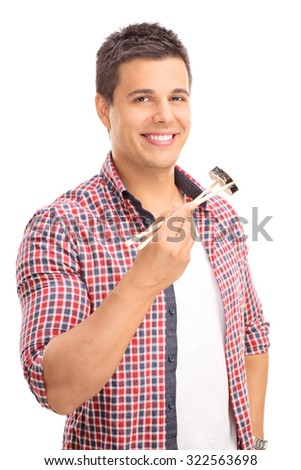 Vertical shot of a young man eating sushi with Chinese sticks and looking at the camera isolated on white background - stock photo