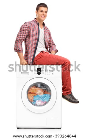 Vertical shot of a young man waiting for the laundry seated on a washing machine isolated on white background - stock photo