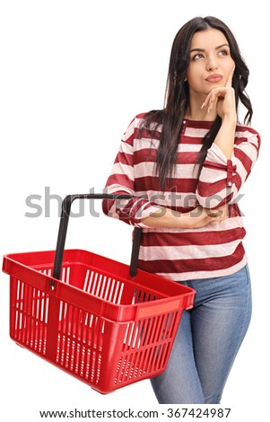 Vertical shot of a young woman holding an empty shopping basket and thinking isolated on white background