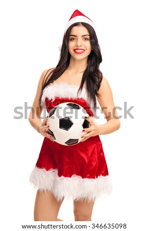 Vertical shot of a young woman in Santa outfit holding a football and looking at the camera isolated on white background