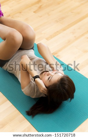 Vertical shot of an Asian lady doing her sit ups exercise in a gym. - stock photo
