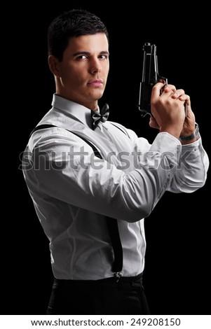 Vertical shot of an elegant man holding a gun on black background - stock photo