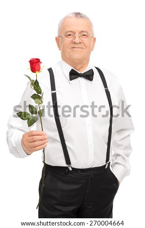 Vertical shot of an elegant senior gentleman holding a red rose, smiling and looking at the camera isolated on white background - stock photo