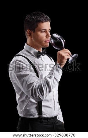 Vertical shot of an elegant young man tasting red wine on black background - stock photo