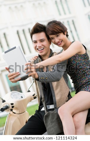 Vertical shot of an excited couple sitting on scooter and looking at the screen of a touchpad - stock photo