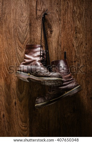 Vertical shot of an old pair of brown boots hanging on a wooden wall - stock photo