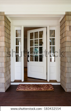 Of an open wooden front door from the exterior of an upscale home