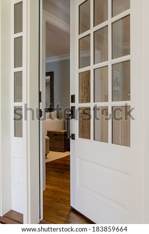 Vertical shot of an open, wooden front door from the exterior of an upscale home with windows.  - stock photo
