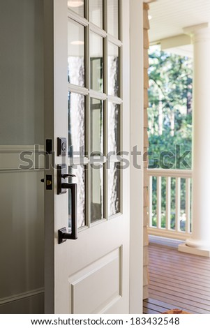Vertical shot of an open, wooden front door from the interior of an upscale home with windows.  - stock photo