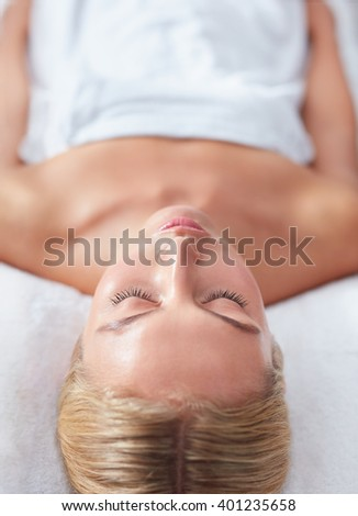 Vertical shot of beautiful woman waiting for a massage at a wellness spa, with focus on face. - stock photo