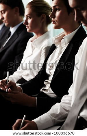 Vertical shot of business people sitting in a row at the conference - stock photo