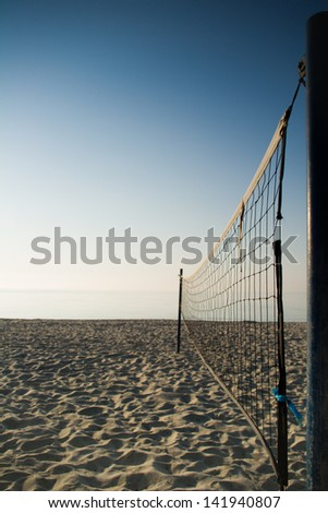 Vertical shot of empty beach volleyball field. Net is in first plane.