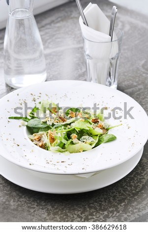 Vertical shot of green salad with spinach and blue cheese - stock photo