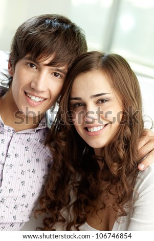 Vertical shot of happy sweethearts smiling at camera - stock photo