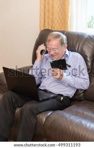 Vertical shot of pensioner using modern electronic devices like laptop and mobile phone