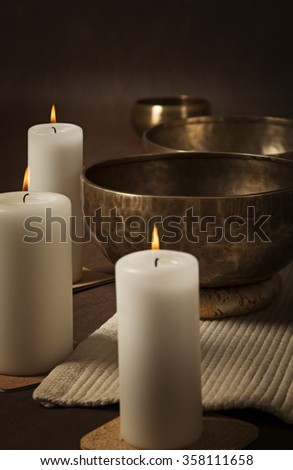 Vertical shot of Tibetan singing bowls with burning candles close-up - stock photo