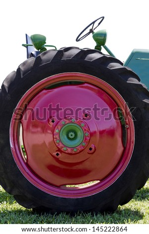 Vertical Shot Of Vintage Red Tractor Wheel/ With Copy Space On Red - stock photo