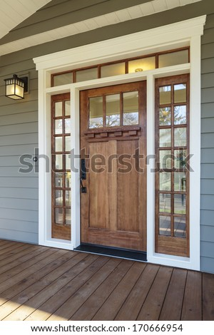 Vertical shot of wooden front door  of an upscale home with windows/Exterior shot of a Wooden Front Door - stock photo