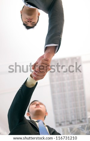 Vertical shot of young business people shaking hands to conclude the deal - stock photo