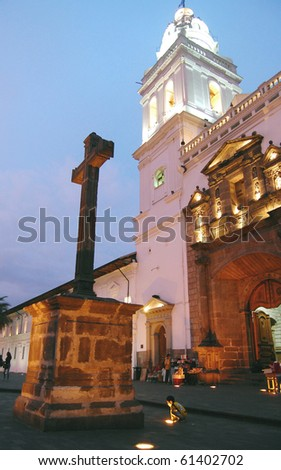 Vertical side view of the Santo Domingo church at dusk, with a baby boy in the foreground, in Quito Ecuador, South America. - stock photo