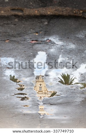 Vertical sidewalk with puddles of water and mirroring image - stock photo