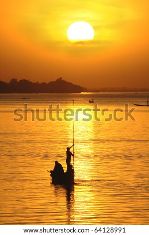 Vertical silhouette of African fisherman in canoe at sunset - stock photo