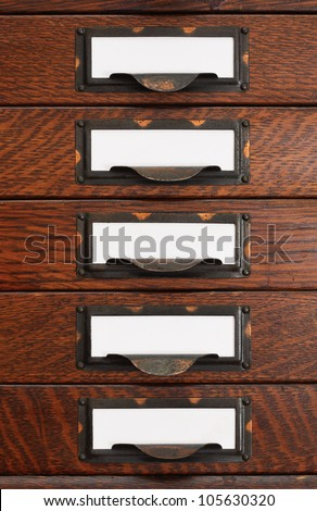 Vertical stack of five old oak flat file drawers with white empty tags in tarnished brass label holders. - stock photo