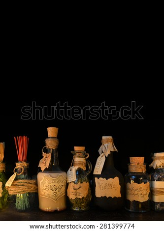 Vertical still life with witch bottles on black. Halloween or homeopathic image. Signs on labels are not foreign text, these letters are imaginary, fictional symbols. - stock photo