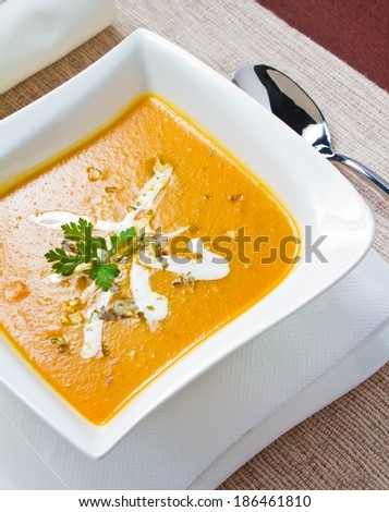 Vertical studio shot of a Pumpkin soup bowl with spoon and napkin - stock photo