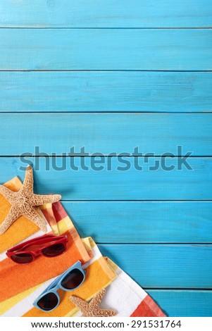 Vertical summer beach background, sunglasses, blue wood deck, copy space - stock photo