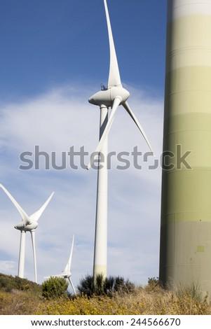 vertical three wind turbine generators in windy valley  - stock photo