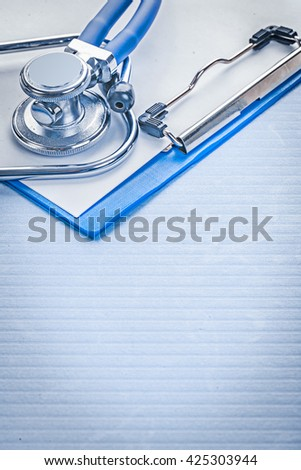vertical version stethoscope on clipboaqrd close up. - stock photo