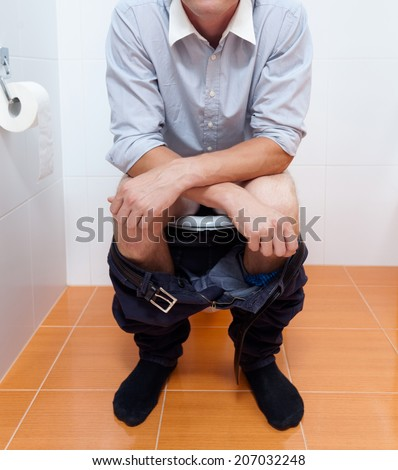 Vertical view of a businessman in toilet - stock photo