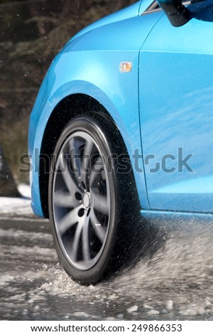 Vertical view of a car tire driving and splashing on the snow.  Driving on a snowy road.