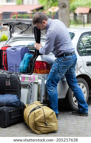 Vertical view of a man packing car for vacation - stock photo