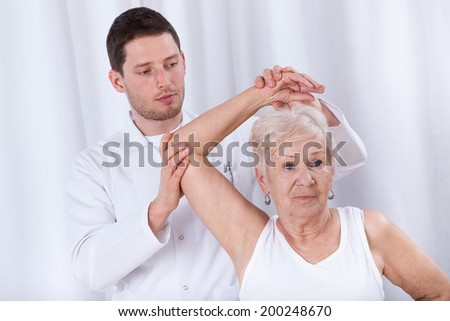 Vertical view of a physiotherapist rehabilitating elderly woman - stock photo