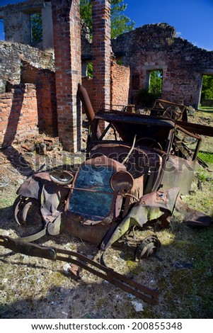 Vertical view of a rusty old car in Oradour sur Glane, France. Abandoned rusty old car. - stock photo