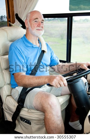 Vertical view of a senior man driving his motor home. - stock photo