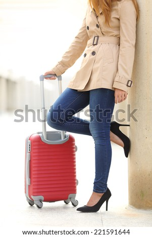 Vertical view of a tourist woman legs waiting with a suitcase in an airport or station - stock photo