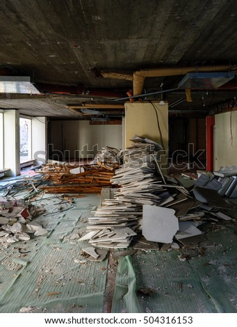 Vertical view of abandoned interior of a business store market with lots of damaged lamps, walls
