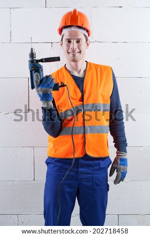 Vertical view of an engineer with the drill - stock photo