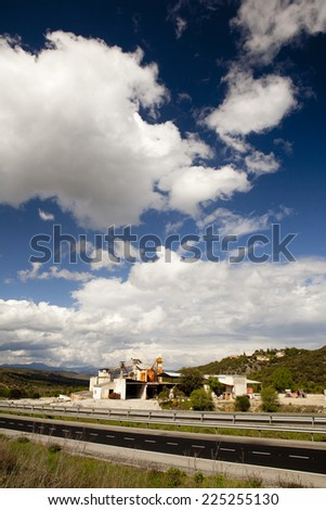 Vertical view of an old factory under the clouds. Clouds over a withe factory - stock photo