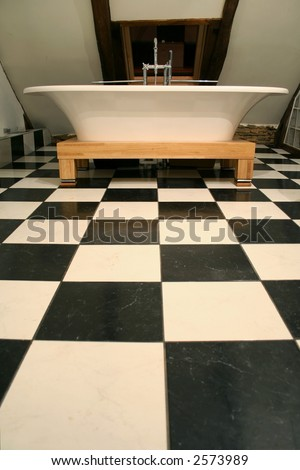 vertical view of bathtub on black and white tile floor - stock photo