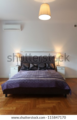 Vertical view of bedroom with violet bed - stock photo