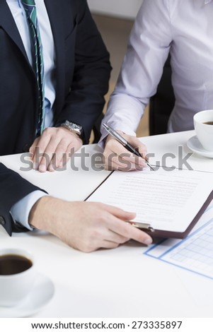 Vertical view of businessperson signing important document
