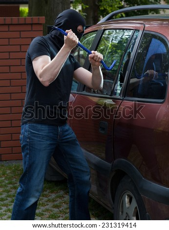 Vertical view of car thief using crowbar - stock photo