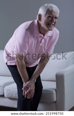 Vertical view of pensioner having knee arthritis - stock photo