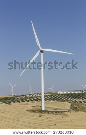 Vertical view of windmill with pastures in the foreground, and olive groves and farm in the background - stock photo