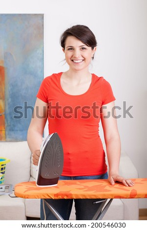 Vertical view of young housewife during ironing - stock photo